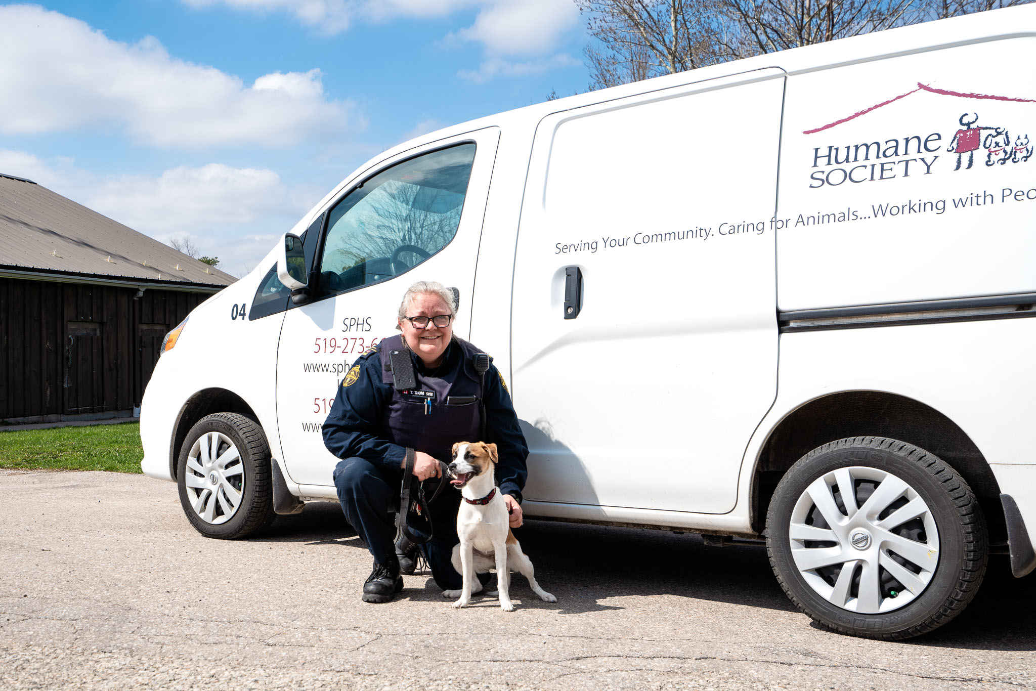 Photo of an Animal Control Officer and a dog beside a Humane Society van
